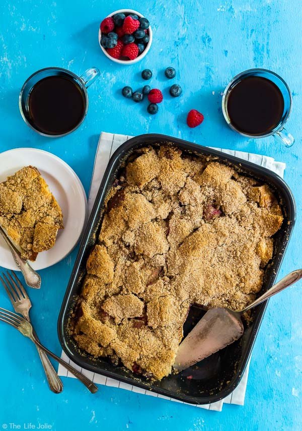 An overhead image of Baked French Toast with a piece taken out and on a plate next to it and coffee, forks and berries around it.