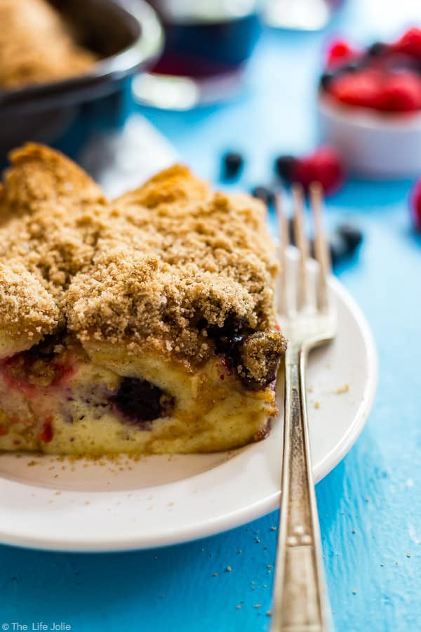 A photo of a piece of Baked French Toast on a white plate with a fork on the side of it and coffee and berries in the background.