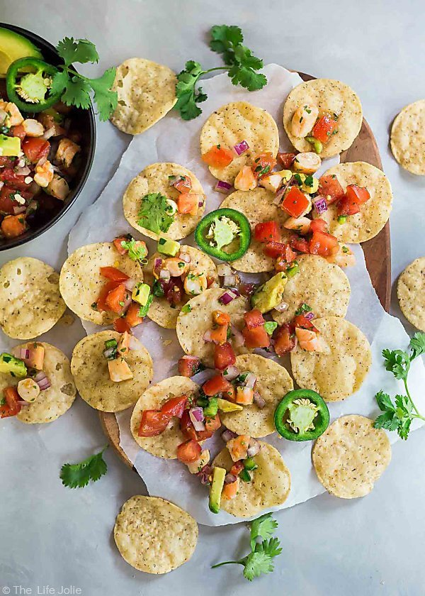 An overhead shot of tortilla chips spread out on a table with 10 Minute Shrimp Salsa on them and the edge of a bowl of 10 Minute Shrimp Salsa being cut off in the upper left corner.