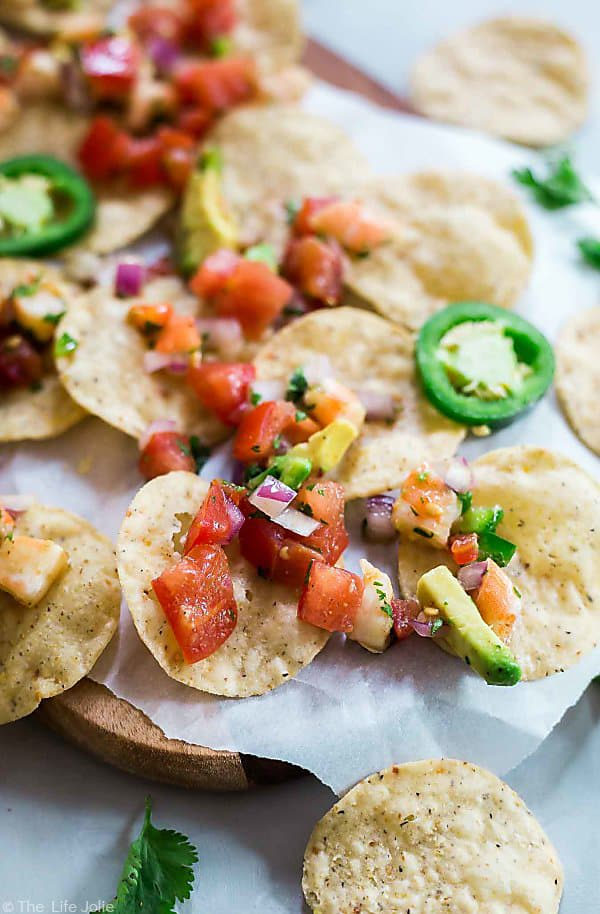 A close up shot of tortilla chips with 10 Minute Shrimp Salsa on them.