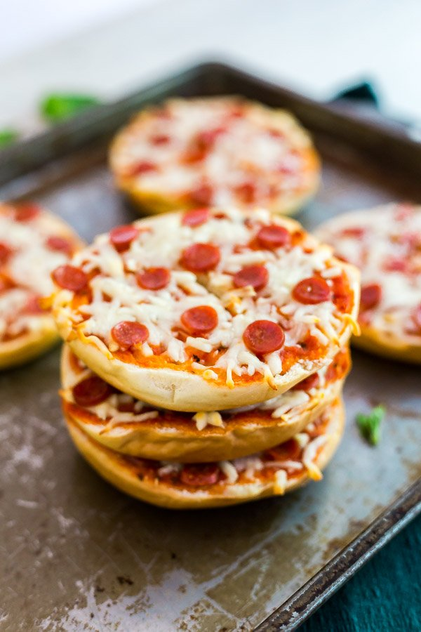 A stack of Freezer Friendly Pizza Bagels on a pan with others out of focus.