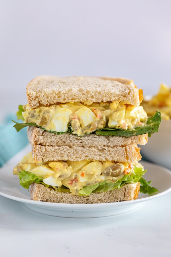 A close up, straight on image of two halves of an egg salad sandwich on top of each other.