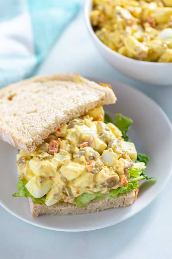 A sandwich with the top off revealing egg salad