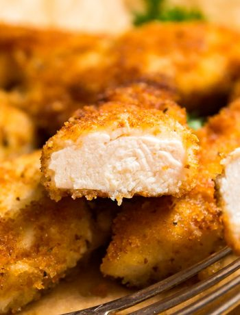 A square image of a chicken cutlet cut in half revealing the cooked inside positioned on top of other chicken cutlets.
