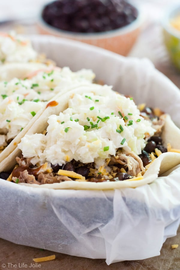 This BBQ Pulled Pork Tacos recipe is a fun twist on traditional mexican tacos. The pulled pork is super easy to make in the crockpot or a great way to use pulled pork leftovers. I make this with slaw and a bunch of other tasty ingredients. Click on the photo to get the recipe!