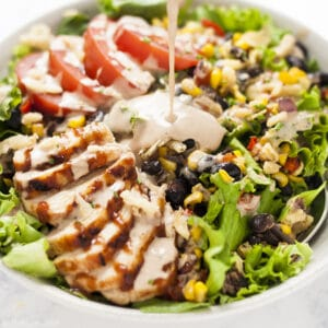 A square image of a close up image of bbq ranch dressing bring poured on a green salad with chicken, corn, black beans and tomatoes in a white bowl.