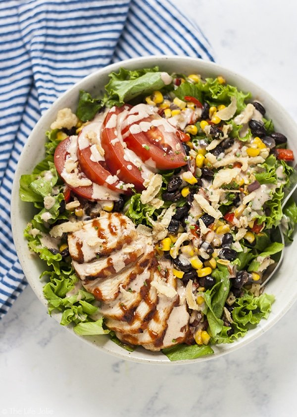 An overhead image of Panera bbq chicken salad in a white bowl with a blue and white stripe napkin next to it.
