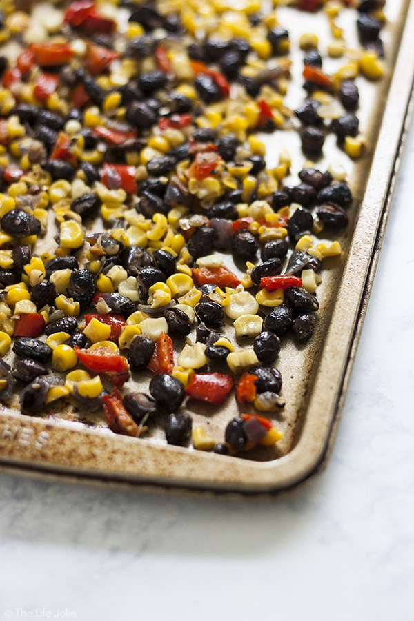 This Roasted Corn Salsa recipe is an easy and healthy addition to a salad, meat based dinner entree or eggs in the morning. It's homemade with black beans, fresh corn, onions and peppers- I seriously love this so much I now keep a container of it in my refrigerator to use throughout the week!