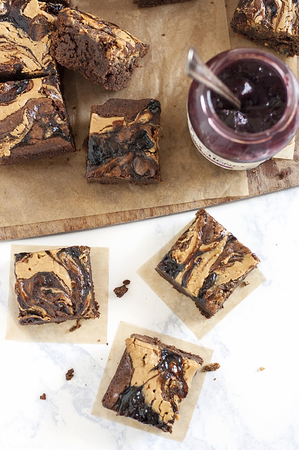 These homemade PB&J Brownies are an easy and delicious holiday dessert option. Chewy, fudgey chocolate brownies with a swirl of peanut butter and the fruit spread of your choice on top, these are made from scratch and would be great on a Thanksgiving of Christmas dessert table or just because you deserve a tasty dessert!