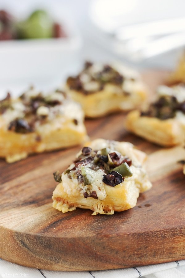 This Olive and Gruyere Puff Pastry Tartlets recipe is one of my new favorite easy appetizers to throw together! Just four simple ingredients (including frozen puff pastry dough, olives and cheese) and they come together quickly for the holidays or any parties you may be having!