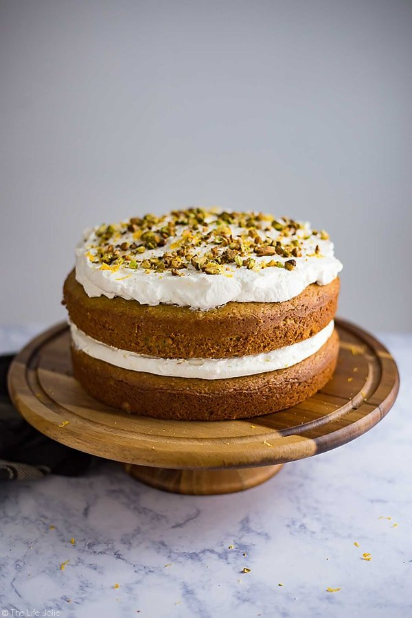 This Lemon Pistachio Cake is the best easy recipe when you need a quick cake to wow your guests. This is actually a hack for a box cake mix made with pudding and topped with light and fluffy whipped cream. The result is a super moist and pretty layered cake that is so good your guests will never guess that it's only halfway homemade!