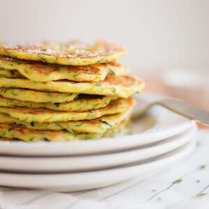 What to do with that bumper crop of zucchini? Zucchini Pancakes! Made with Bisquick, Romano cheese, shredded zucchini, butter, garlic powder and onion, they are a super easy savory breakfast and are also a great make-ahead appetizer for a party!