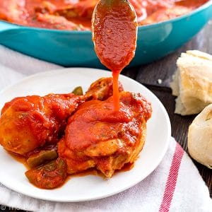 A square image of a spoon pouring extra cacciatore sauce on top of chicken pieces on a plate with a pan of chicken behind it and bread on the side.