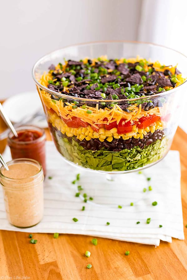 This 7 Layer Taco Salad is an easy recipe to make for parties. Full of delicious Mexican-inspired flavors it's got seven (or more) layers of things like beans, cheese, corn, tomatoes and is served with a creamy taco ranch dressing. Top it with chicken for a healthy main dish or serve it on it's own as great side dish to pass. This is perfect to bring to a Cinco de Mayo get together!