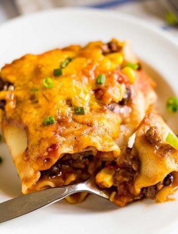 Mexican Lasagna Roll-ups are a delicious combination of two family favorites: Lasagna and Tacos. This is an easy recipe featuring meat, cheese, beans, corn, tomatoes and rolled up in lasagna noodles. They're total comfort food and great for when you're cooking for family and friends!
