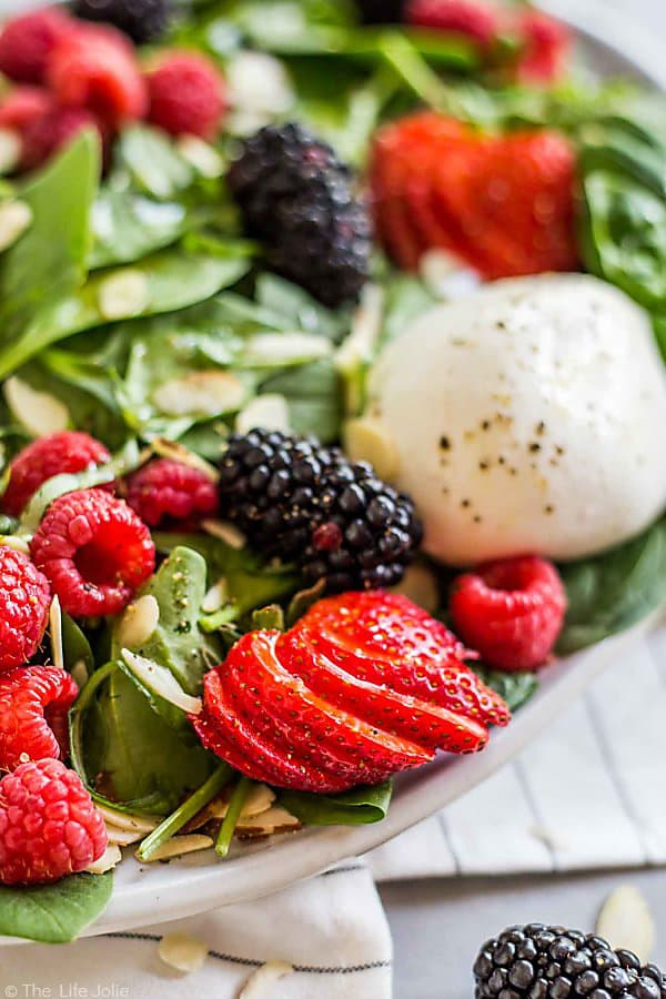 A close up of the strawberry in the Summer Berry and Burrata Salad.