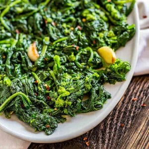 A square photos of broccoli rabe with garlic on a plate.