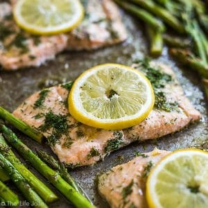 A square photo of Lemon Dill Salmon lined up on the diagonal surrounded by other pieces of salmon which are out of focus and asparagus which is also out of focus.