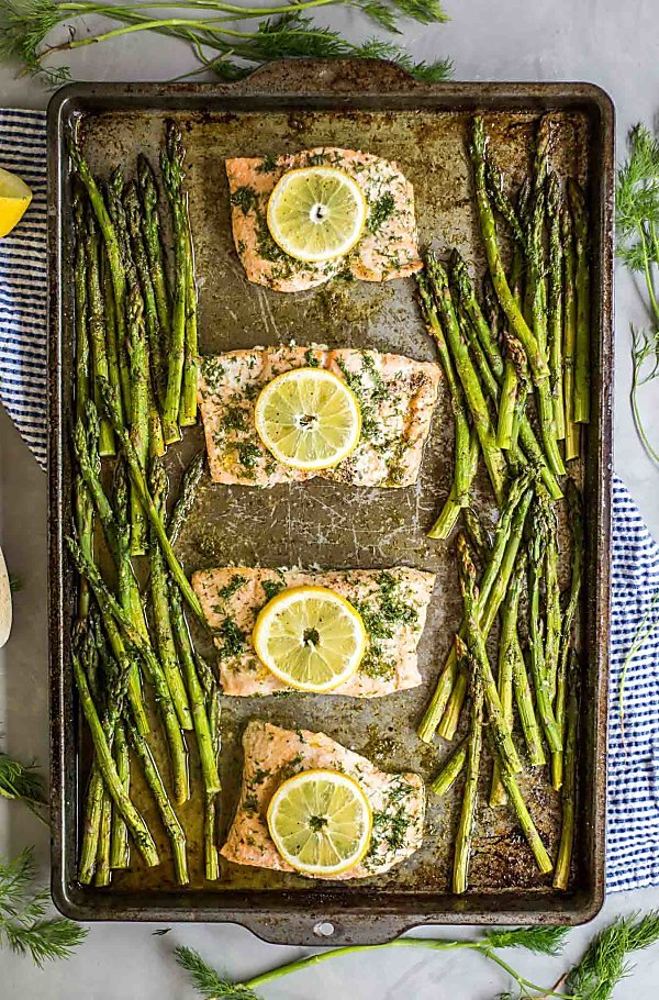 A vertical, overhead view of the baked Salmon and asparagus on a sheet pan with a towel underneath it and surrounded by fresh dill and squeezed lemons.