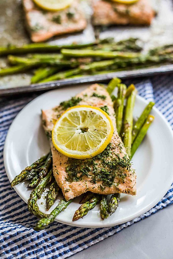A photo focused on a plate of Lemon Dill Salmon sitting atop asparagus spears with a lemon round on top of the Salmon and a blurry plan of other pieces of salmon and asparagus in the background.