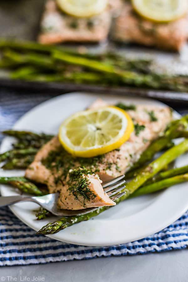 A bite of this baked salmon recipe on a fork sitting atop a plate with the rest of the piece of salmon and some asparagus spears in the background with a sheet pan of other pieces of salmon and asparagus behind the plate and out of focus.