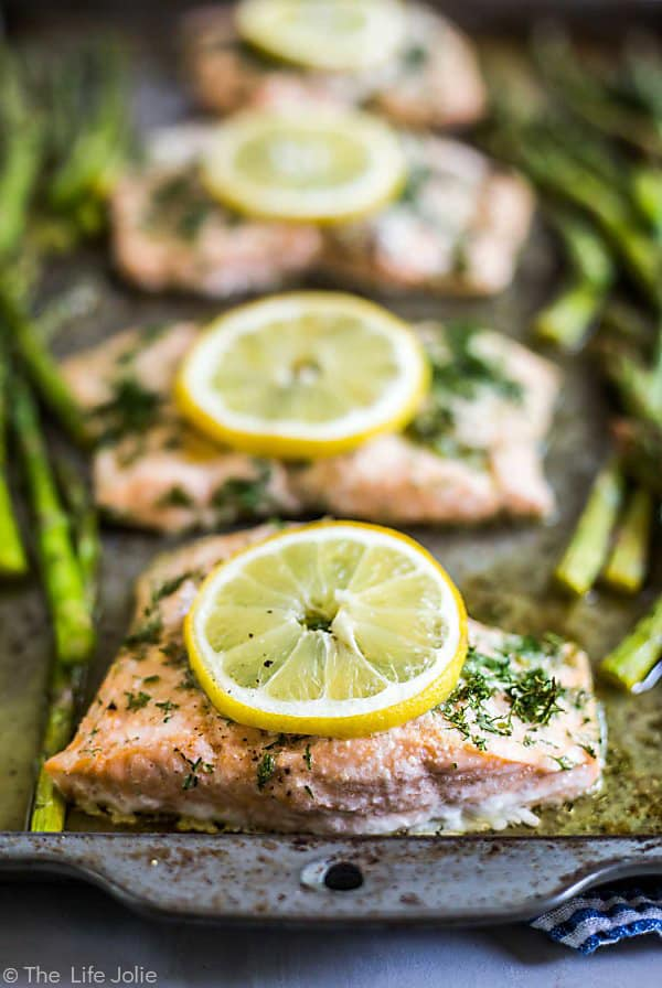 A row of 4 pieces of lemon Dill Salmon with lemon rounds on each piece on a sheet pan with the front piece of in focus and the others lined up behind it out of focus and asparagus on either side of the salmon, also out of focus.