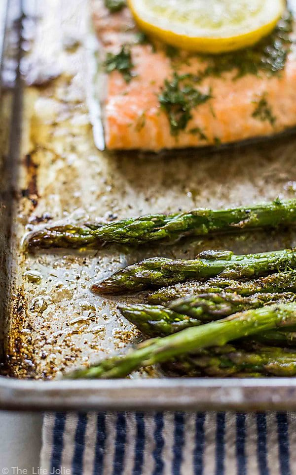A close up photos of the tips of asparagus spears with the front of the sheet pan blurry in the foreground and a blurry piece of Lemon Dill Salmon with a lemon round on top in the background.