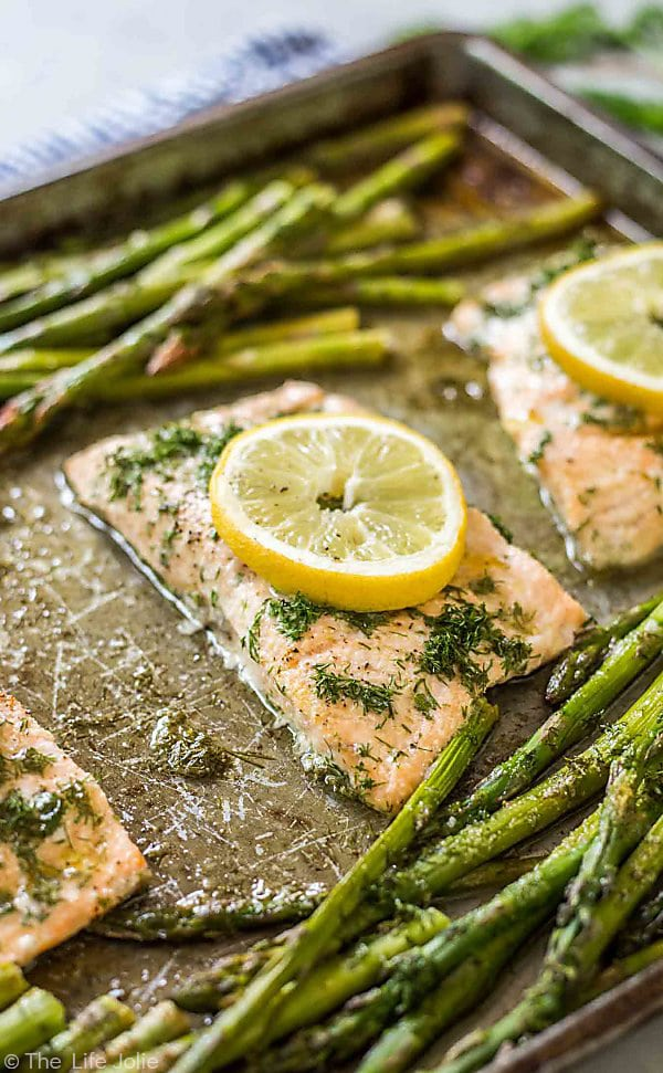 A close up photo of a cooled piece of salmon at a diagonal angle sprinkled with fresh dill with a lemon round placed on top and asparagus and other pieces of salmon are ourt of focus all around the main piece of salmon.