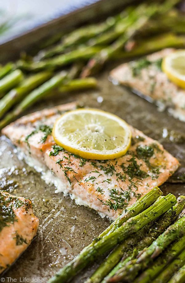 Lemon Dill Salmon on a sheet pan sitting at a diagonal with out pieces of salmon and asparagus out of focus.
