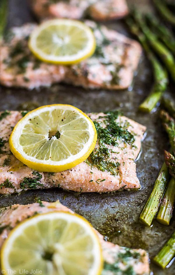 Four pieces of Lemon Dill Salmon lined up on a sheet pna with the left sides of the salmon cut off. The second piece of salmon is in focus and the two pieces in the back and the one piece in the foreground are out of focus along with the asparagus spears to the right of the salmon.