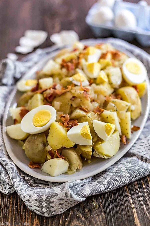 German Potato Salad on a gray towel with eggs and egg shells in the background.