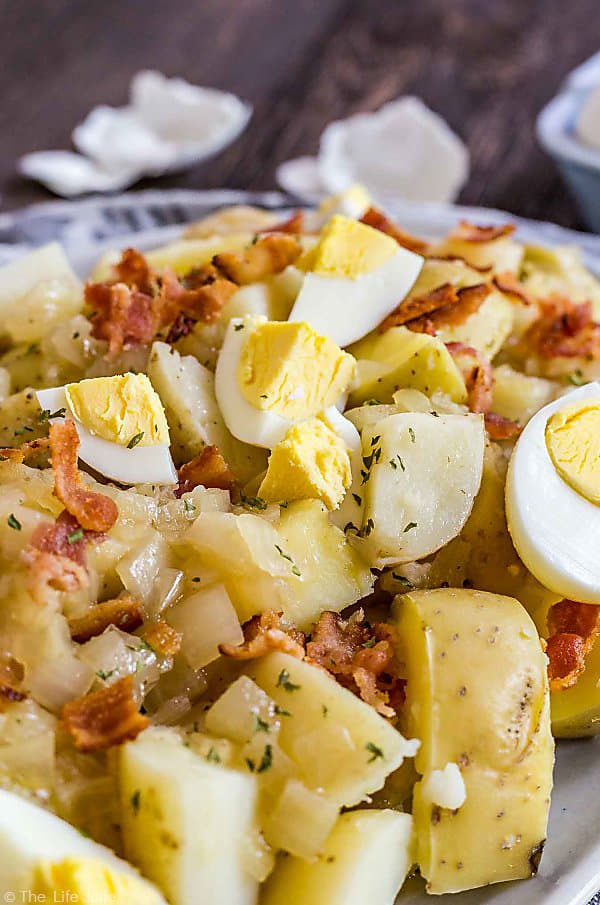 A close up shot of the hard boiled egg in German Potato Salad.