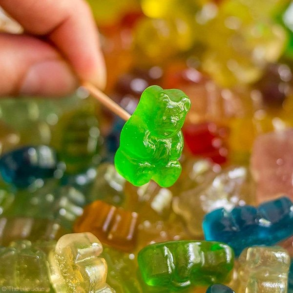 A square image of a hand holding a toothpick with a boozy gummy bear on it with a bunch of the gummy bears behind it.