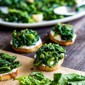 A square image of Broccoli Rabe and Ricotta Crostini with a yellow broccoli rabe blossom in the foreground and some other crostini and a plate of broccoli rabe in the background.
