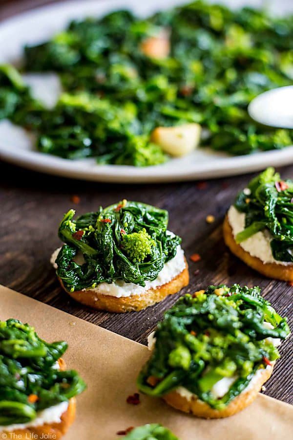 An image of Broccoli Rabe and Ricotta Crostini with a blurry crostini in the foreground and the blurry plate of broccoli rabe in the background.