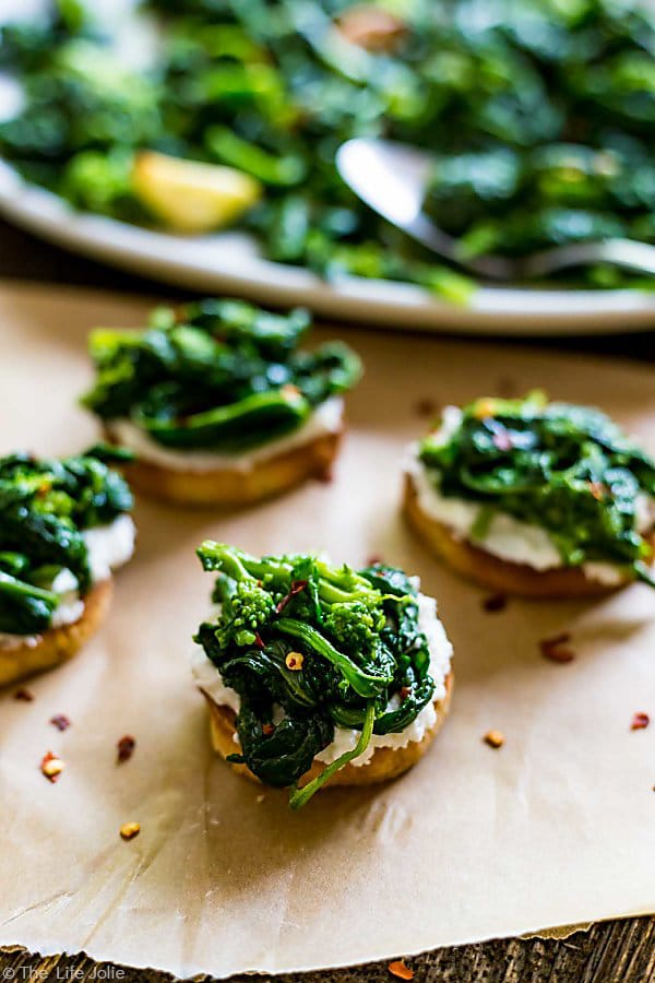 A couple Broccoli Rabe and Ricotta Crostini's on a piece of parchment paper with crushed red pepper flakes surrounding it and a plate of broccoli rabe in the background.
