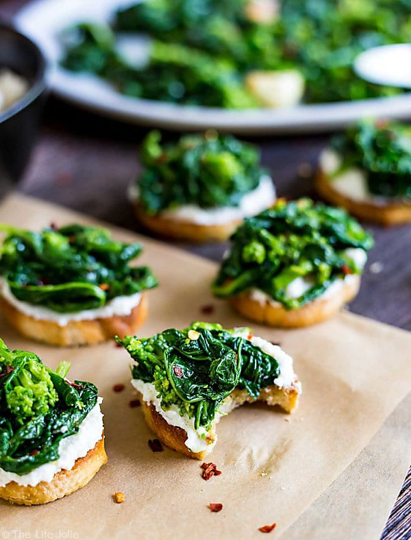 A piece of Broccoli Rabe and Ricotta Crostini with a bite taken out of it in the front and other crostinis in the background and out of focus.