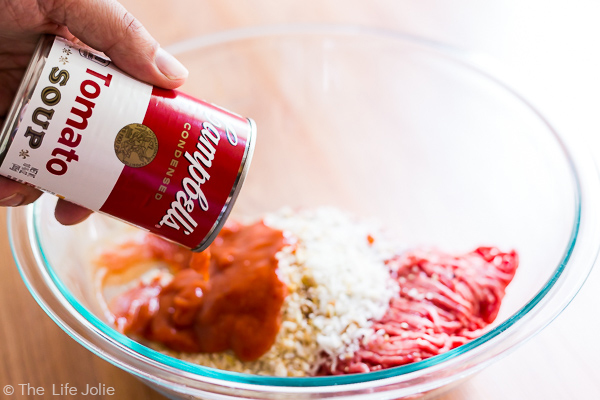 Campbell's tomato soup being poured into a bowl of meatball ingredients.