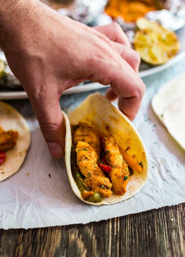 A hand pickig up a fajita made from Foil Packet Chicken Fajitas.
