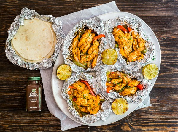 An overhead image of Foil Packet Chicken Fajitas on a platter with some tortillas and Simply Organic Ancho Chili Powder.