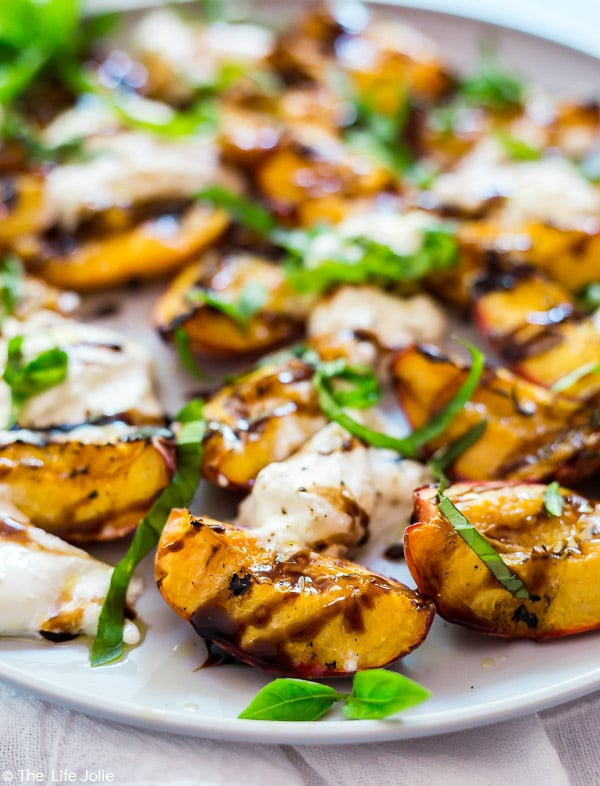 A close up image of a peach in the Grilled Peaches and Burrata Salad with balsamic drizzled on it and fresh basil leaves with the rest of the salad behind it and out of focus.