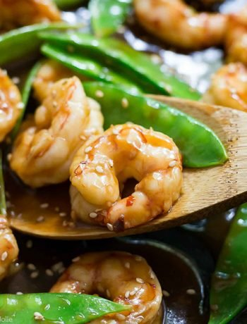 A square image of Shrimp and Snow Peas Stir Fry in a pan with a piece of shrimp on a wooden spoon.