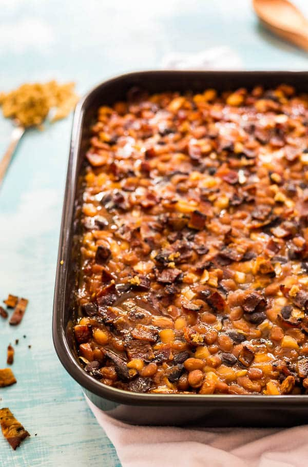 A shot of the left side of a pan of Most Delicious Baked Beanswith a spoon of brown sugar and some bacon crumbled on the side of it.