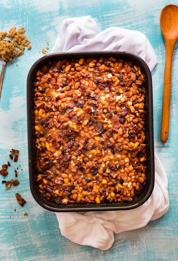 An overhead image of Most Delicious Baked Beans on a white cloth with a blue background, some crumbled bacon, a wooden spoon and an overflowing spoonful of brown sugar.