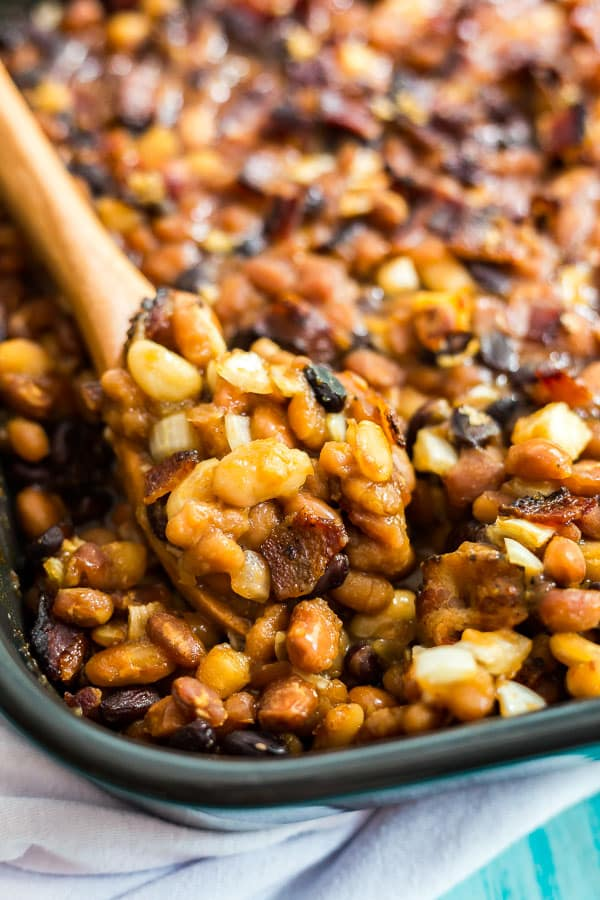 A close up image of the corner of a pan of Most Delicious Baked Beans with a spoon in it.