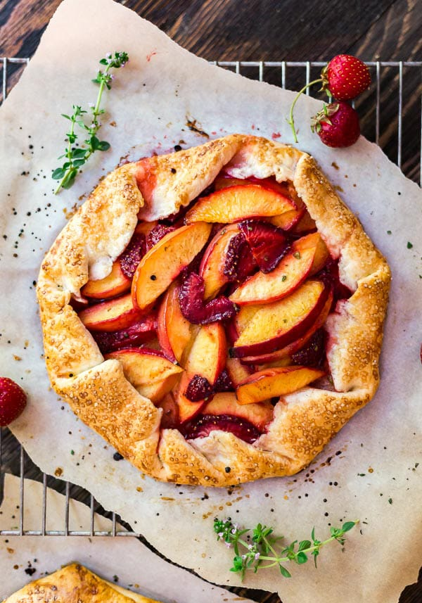 An overhead shot of the Nectarine and Strawberry Galette with Thyme on parchment paper woth some sprigs of fresh thyme and strawberries around it.