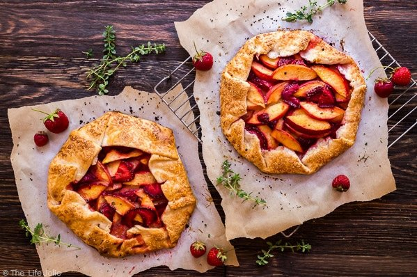 An overhead image of two Nectarine and Strawberry Galette's with Thymeon parchment paper with a wood background and fresh thyme and strawberries surrounding it,