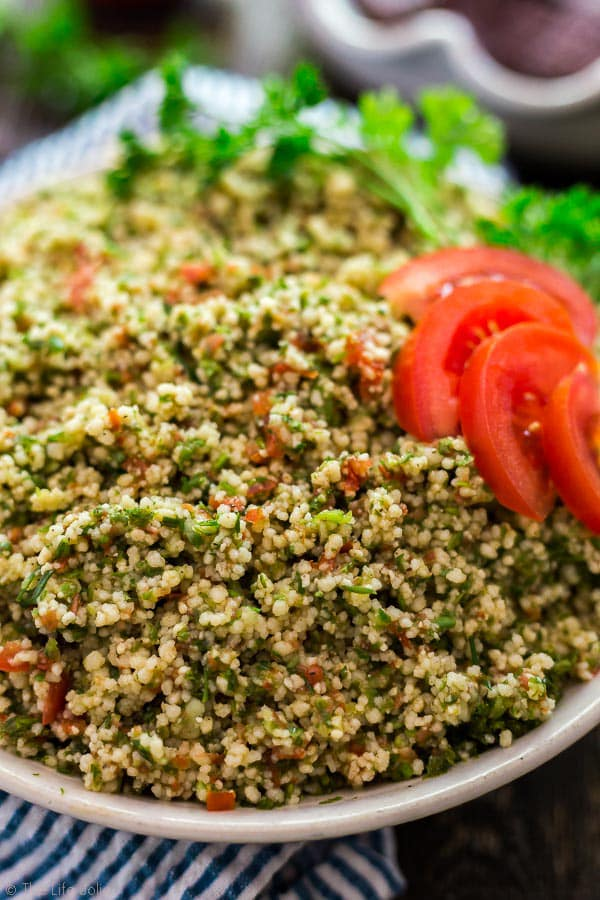 A close up image of Easiest Ever Tabouli garnished with tomato and parsley with the sides cut off by the camera.