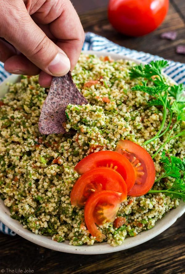 An image of a man's hand dipping blue tortilla chip into a bowl of Easiest Ever Tabouli that is garnished with sliced tomato and parsley.
