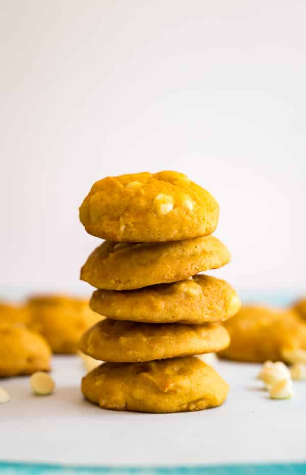 A straight on shot of White Chocolate Macadamia Nut Pumpkin Cookies with other cookies behind it out of focus.